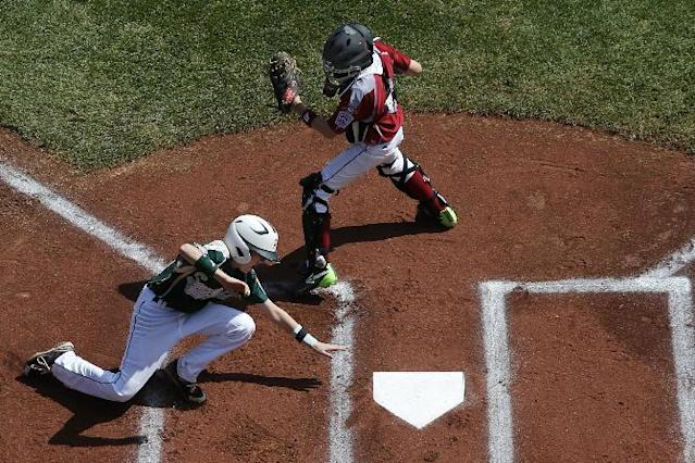 Pearland's Michael Groover, bottom, scores behind Lynnwood catcher Robley Corsi III on a single by Pearland's Matthew Adams off Lynnwood pitcher Logan Kruse during the first inning of an elimination baseball game against Lynnwood at the Little League World Series tournament in South Williamsport, Pa., Monday, Aug. 18, 2014. Pearland won 11-4. (AP Photo/Gene J. Puskar)