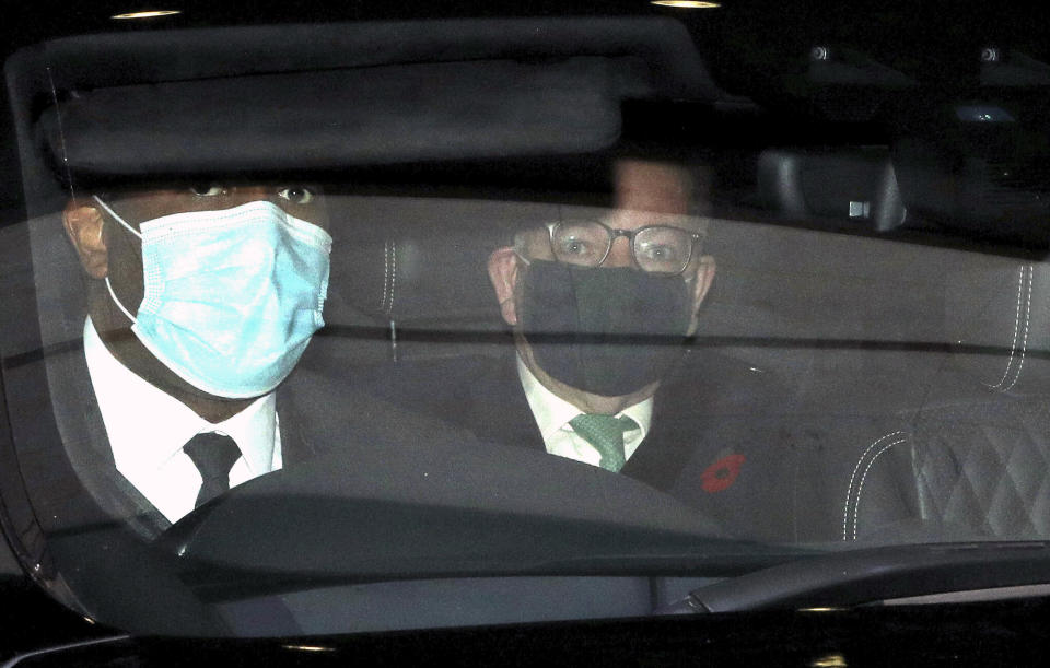 British lawmaker Michael Gove, right, is driven away following his appearance on a current affairs TV programme in London, Sunday Nov. 1, 2020. The British government announced on Saturday a four-week public lockdown in response to the coronavirus, but Michael Gove on Sunday acknowledged that the lockdown could be extended. (Jonathan Brady/PA via AP)