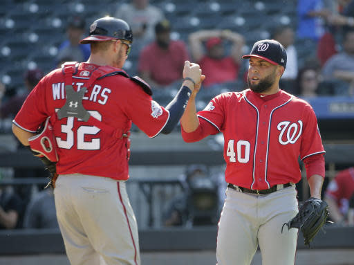 Washington Nationals relief pitcher Kelvin Herrera, right, and catcher Jamie Burke celebrate after the baseball game against the New York Mets at Citi Field, Sunday, July 15, 2018, in New York. The Nationals defeated the Mets 6-1. (AP Photo/Seth Wenig)