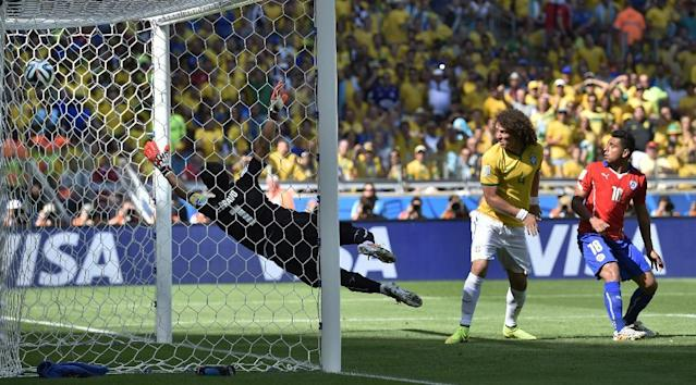 The ball goes into the net past Chile's goalkeeper Claudio Bravo for Brazil's opening goal during the World Cup round of 16 soccer match between Brazil and Chile at the Mineirao Stadium in Belo Horizonte, Brazil, Saturday, June 28, 2014. (AP Photo/Martin Meissner)