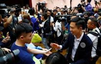 Local candidate Kelvin Lam celebrates with supporters at a polling station in the South Horizons West district in Hong Kong