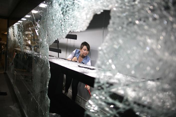 A shop keeper sweeps up broken glass inside a store in the area of Clapham in the aftermath left by riots in London Tuesday, August 9, 2011. Britons swept up, patched up and feared further violence Tuesday, demanding police do more to protect them after three nights of rioting left trails of looted stores, wrecked cars and burned buildings across London and several other cities. (AP Photo/Elizabeth Dalziel)
