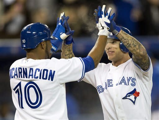 Toronto Blue Jays' Edwin Encarnacion and Brett Lawrie, right, celebrate after scoring against the Boston Red Sox in the sixth inning of a baseball game in Toronto on Tuesday, April 10, 2012. (AP Photo/The Canadian Press, Frank Gunn)