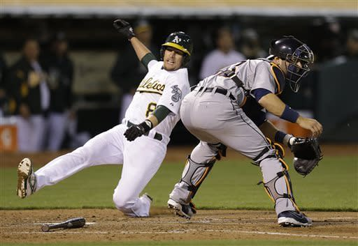 Oakland Athletics' Jed Lowrie, left, slides to score past Detroit Tigers catcher Alex Avila in the sixth inning of a baseball game, Friday, April 12, 2013, in Oakland, Calif. Lowrie scored on a single by A's Josh Reddick. (AP Photo/Ben Margot)