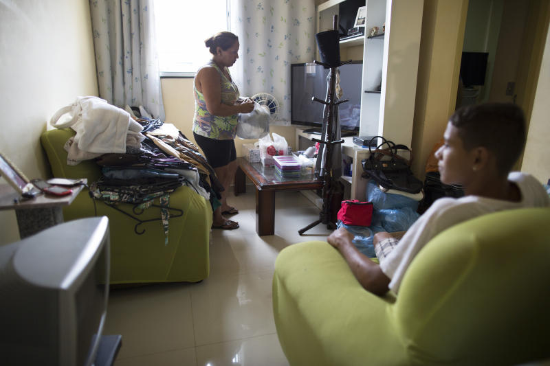 In this Feb. 16, 2014 photo, Dalvaneide Pequeno do Nascimento organizes her apartment as her son looks on at their residence inside the Condominio Oiti project in the suburb of Campo Grande, Rio de Janeiro, Brazil. Nascimento, her husband and children were among the families forced out of their homes in Vila Recreio II, a Rio de Janeiro slum that was razed three years ago to make way for the Transoeste expressway connecting the Barra da Tijuca neighborhood that'll be the main hub for the 2016 Olympics with the western outskirts of Rio. (AP Photo/Leo Correa)