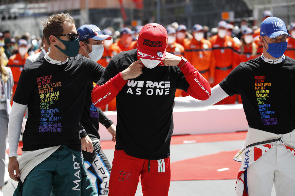 MONTE-CARLO, MONACO - MAY 23: Charles Leclerc of Monaco and Ferrari is embraced by Sebastian Vettel of Germany and Aston Martin F1 Team and Mick Schumacher of Germany and Haas F1 on the grid after finding out he could not start the race during the F1 Grand Prix of Monaco at Circuit de Monaco on May 23, 2021 in Monte-Carlo, Monaco. (Photo by Sebastian Nogier - Pool/Getty Images)