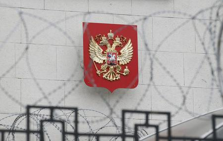 FILE PHOTO: A coat of arms is seen through barbed wire on the wall of the Russian embassy in Kiev, Ukraine March 26, 2018. REUTERS/Gleb Garanich/File Photo