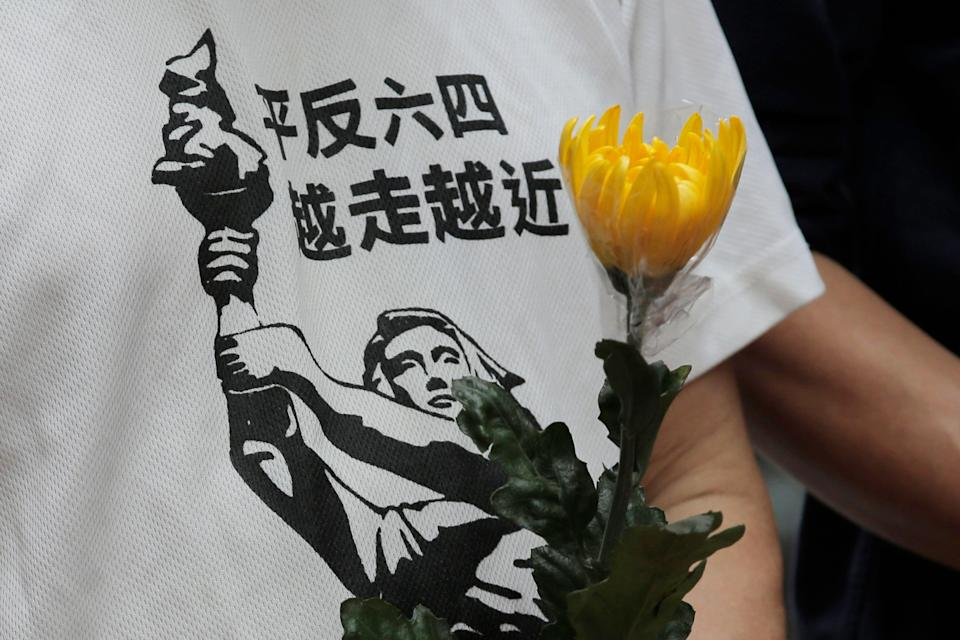"""A protester wearing T-shirt with Chinese words that read """"Exonerate the June 4 protest, move closer"""", holds flower to commemorate the June 4, 1989 military crackdown in Beijing's Tiananmen Square on a pro-democracy student movement, in the University of Hong Kong, Friday, May 4, 2018. Tens of thousands of people are expected to attend an upcoming annual candlelight vigil on June 4 to remember those killed when their protest in Beijing. (AP Photo/Kin Cheung)"""