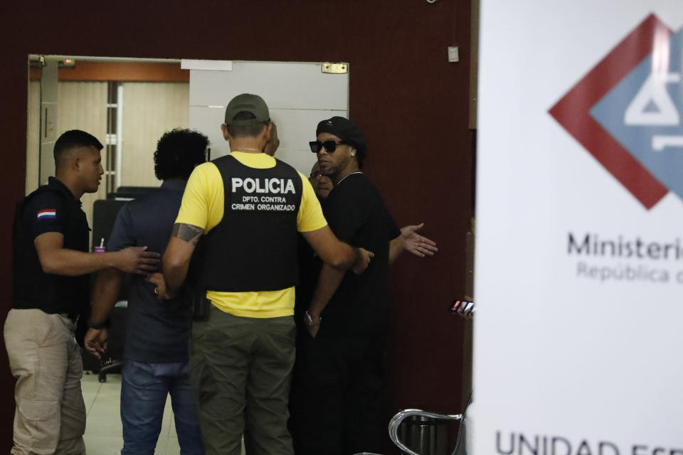 Former Brazilian soccer star Ronaldinho, or Ronaldo de Assis Moreira, right, enters Paraguay's attorney offices in Asuncion, Paraguay, Thursday, March 5, 2020. According to local news, Ronaldinho is accused of arriving in the country with a fake Paraguay passport. (AP Photo/Jorge Saenz)