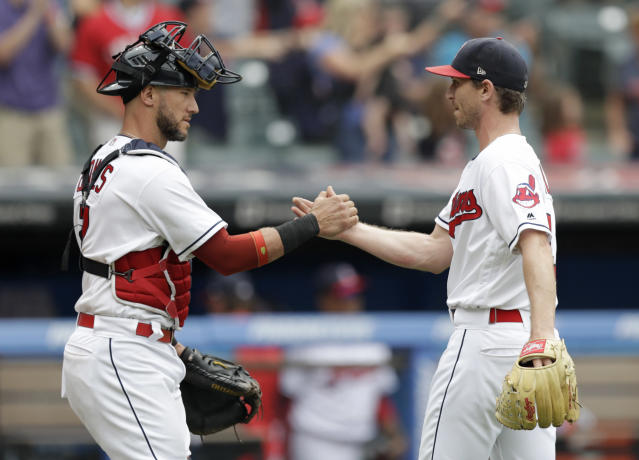 Cleveland Indians' Yan Gomes, left, and relief pitcher Josh Tomlin celebrate after the Indians defeated the Chicago White Sox 12-0 in a baseball game, Wednesday, June 20, 2018, in Cleveland. (AP Photo/Tony Dejak)