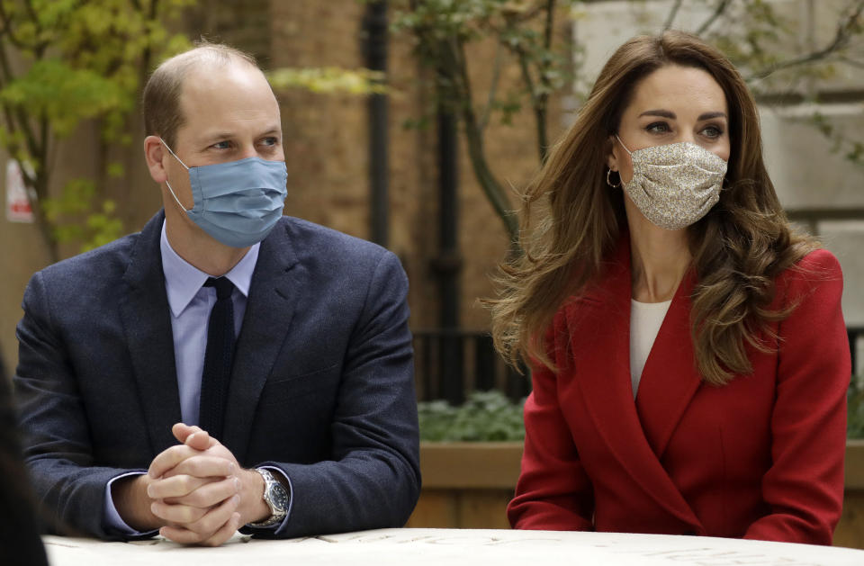 Britain's Prince William and his wife Kate the Duchess of Cambridge meet pharmacist Joyce Duah as they visit St. Bartholomew's Hospital in London, to mark the launch of the nationwide 'Hold Still' community photography project, Tuesday, Oct. 20, 2020. The Duke and Duchess of Cambridge on Tuesday met a small number of staff from the hospital, including pharmacist and photographer Joyce Duah and the two pharmacy technician colleagues she photographed writing on their PPE as they put it on, in a photograph that was selected to be in the set of 100 images taken during the coronavirus lockdown. (AP Photo/Matt Dunham, Pool)