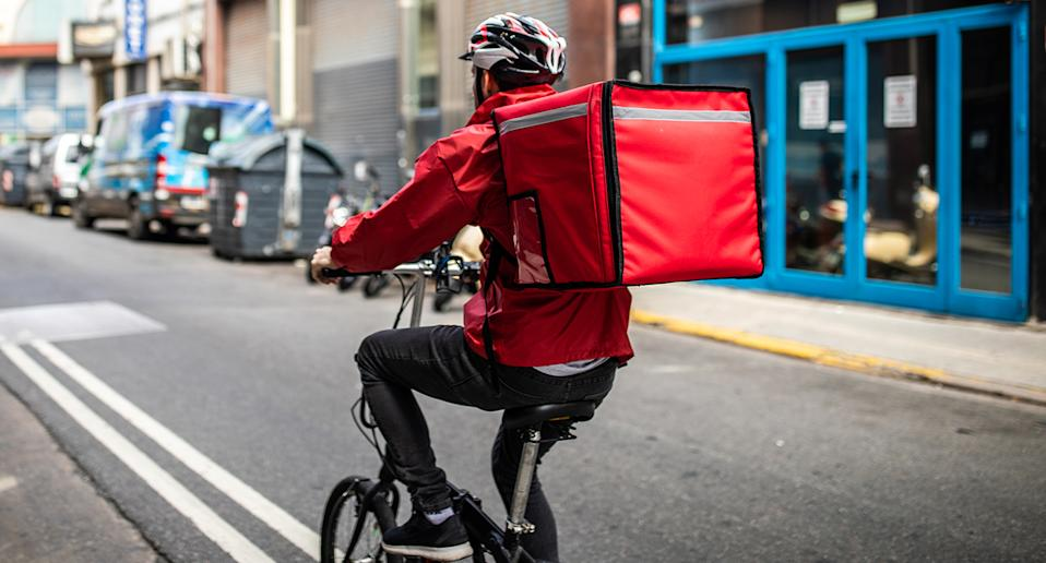 Rear view of ddelivery man, who's wearing cycling helmet and red jacket, riding bicycle on city street on his way to customer