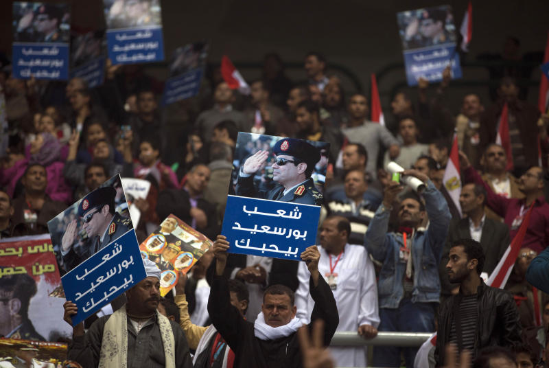 """Egyptians attend a rally holding posters of Egypt's Defense Minister, Gen. Abdel-Fattah el-Sissi, with Arabic writing that reads""""Port Said people love you,"""" in support of el-Sissi, in Cairo, Egypt, Tuesday, Jan. 21, 2014. Supporters of the powerful army chief and defense minister urged Egyptians on Tuesday to turn the third anniversary to 2011 uprising that toppled longtime autocratic president Hosni Mubarak, to a show of gratitude to the general for ousting Islamist president, calling on him to contest elections. (AP Photo/Khalil Hamra)"""