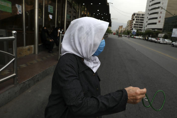A woman holds prayer beads as she crosses an intersection in downtown Tehran, Iran, Tuesday, May 11, 2021. (AP Photo/Vahid Salemi)