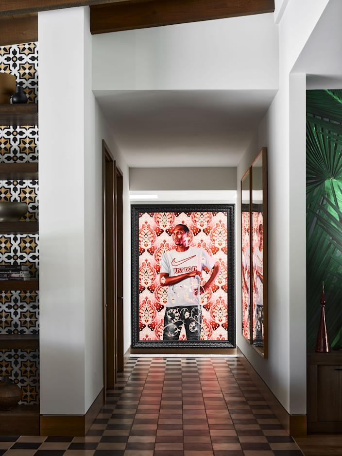 """Kehinde Wiley's 2018 <em>Portrait of Marcus Stokes</em> hangs in the hallway leading to the master suite. """"It's such a strong piece and it fits so perfectly there,"""" says homeowner Craig Hartzman, a longtime Wiley fan who collects contemporary works from both emerging and established artists."""