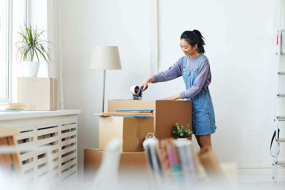 Side view portrait of young Asian woman packing cardboard boxes and smiling happily while moving to new home or apartment, copy space