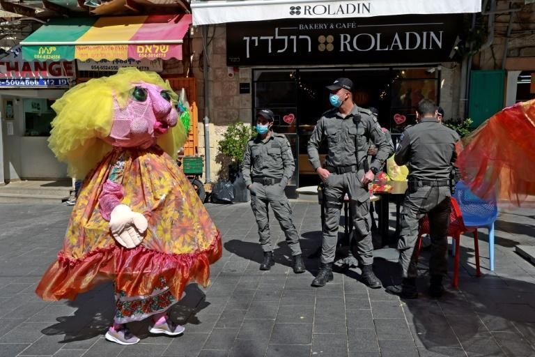 Israelis hold scaled back celebrations for the carnival-like festival of Purim after the government imposed a nightime curfew for fear a new spike in infections could yet overshadow its vaccination campaign