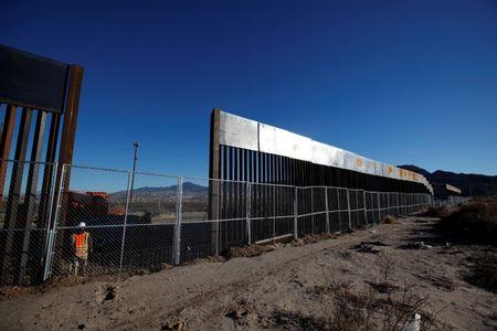 A worker stands next to a newly built section of the U.S.-Mexico border fence at Sunland Park, U.S. opposite the Mexican border city of Ciudad Juarez