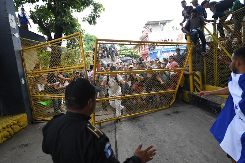 Honduran migrants tear down the gate of the Guatemala-Mexico international border bridge in Ciudad Hidalgo, Mexico (AFP Photo/Pedro Pardo                    )