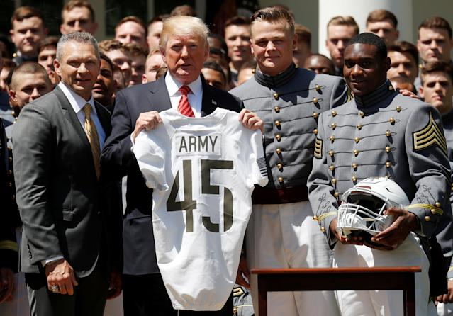 U.S. President Donald Trump poses with Coach Jeff Monken (L) and team captains John Voit and Ahmad Bradshaw during the ceremony wherein Trump presented the Commander-in-Chief's Trophy to the U.S. Military Academy football team in the Rose Garden at the White House. (REUTERS/Leah Millis)