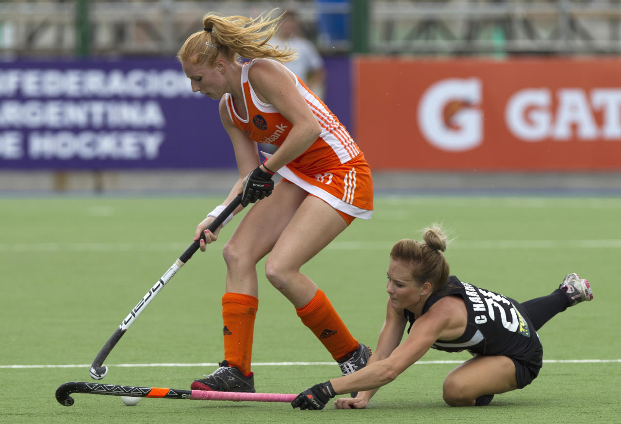 The Netherlands' Margot van Geffen, left, battles for the ball with New Zealand's Charlotte Harrison during their Women's Champions Trophy quarterfinal field hockey match in Rosario, Argentina, Thursday Feb. 2, 2012. (AP Photo/Eduardo Di Baia)
