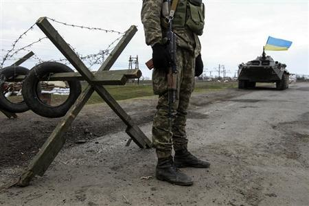 A Ukrainian soldier and armored personnel carrier guard a checkpoint near the village of Salkovo