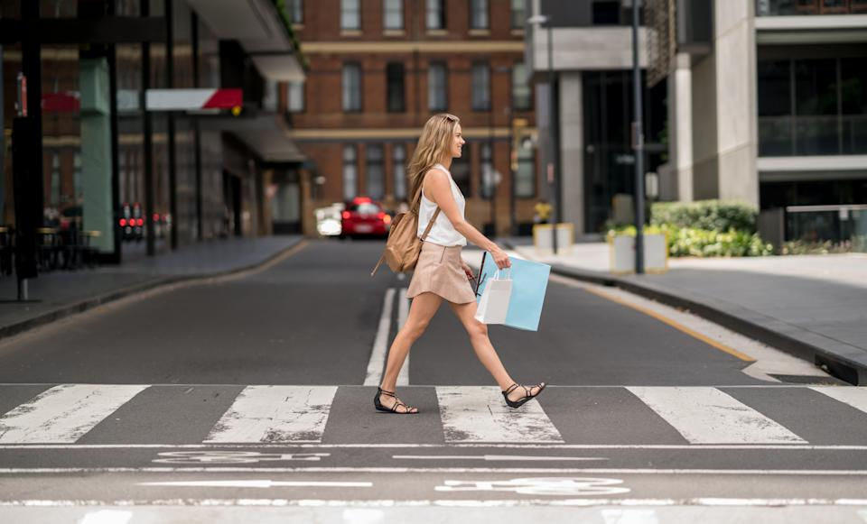 Woman crossing the street and carrying bags