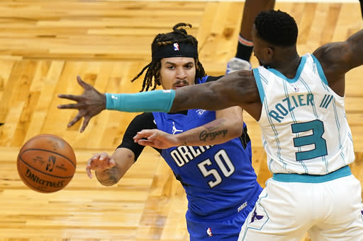 Orlando Magic guard Cole Anthony (50) passes the ball around Charlotte Hornets guard Terry Rozier (3) during the second half of an NBA basketball game, Sunday, Jan. 24, 2021, in Orlando, Fla. (AP Photo/John Raoux)