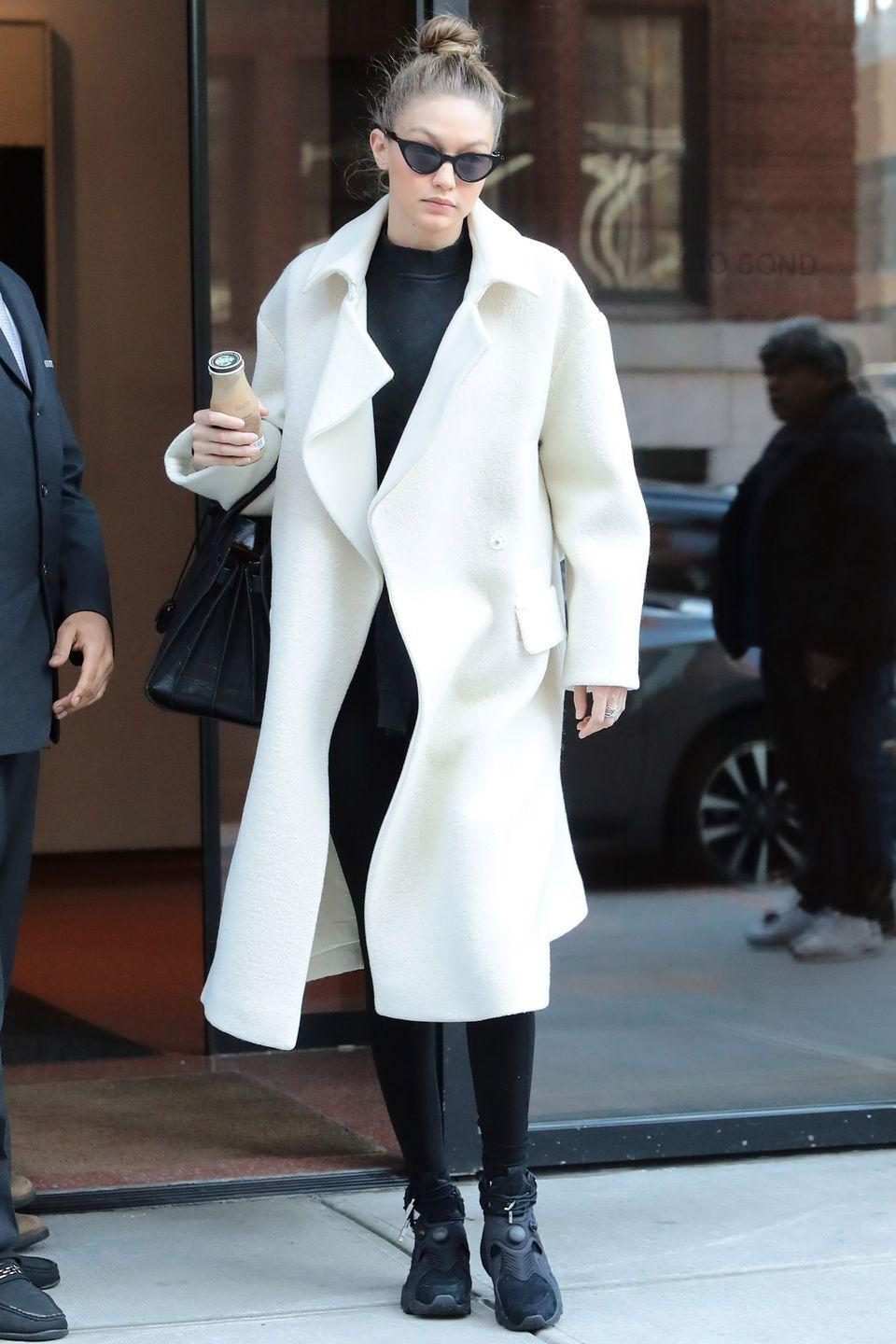 <p>In a white coat, black workout gear, black high-top sneakers, a black tote bag and black cat eye glasses while out in New York.</p>