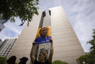 A woman holds a sign of George Floyd in front of the Hennepin County Government center during the sentencing hearing Friday, June 25, 2021, in Minneapolis, of former Minneapolis police officer Derek Chauvin who was sentenced to 22 1/2 years in prison for the murder in May, 2020 of Floyd during an arrest in Minneapolis. (AP Photo/Christian Monterrosa)