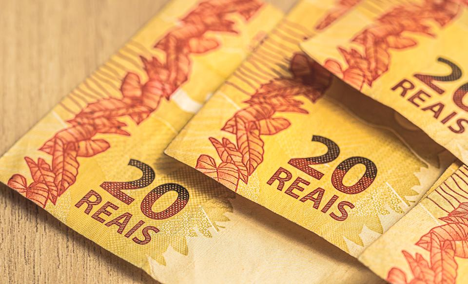 Real - Brazilian Currency. Money, Brazil, Dinheiro, Reais. Group of 20 Reais banknotes on a wood objetc.