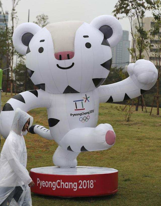 <p>A woman walks by an official mascot of the 2018 PyeongChang Olympic Winter Games, white tiger Soohorang, before the event to mark the start of the 500-day countdown in Seoul, South Korea, Tuesday, Sept. 27, 2016. With 500 days until the Olympic cauldron is ignited in Pyeongchang, organizers of the 2018 Winter Games say 90 percent of construction on new venues is complete and the focus of preparations is on test events. (AP Photo/Lee Jin-man) </p>