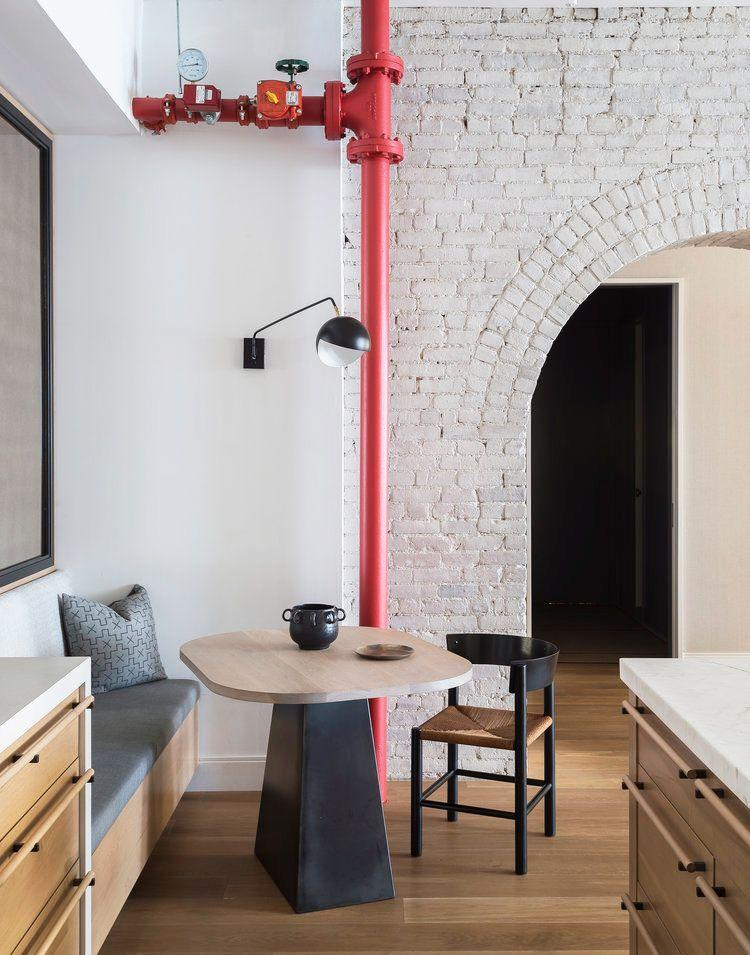 <p>Rather than seeing the exposed pipe in this kitchen as a design flaw, Studio DB saw an opportunity for a fun pop of red. Now it looks like an edgy, industrial, unique, and colorful accent that anchors the kitchen and puts the stylish breakfast nook in the spotlight. </p>