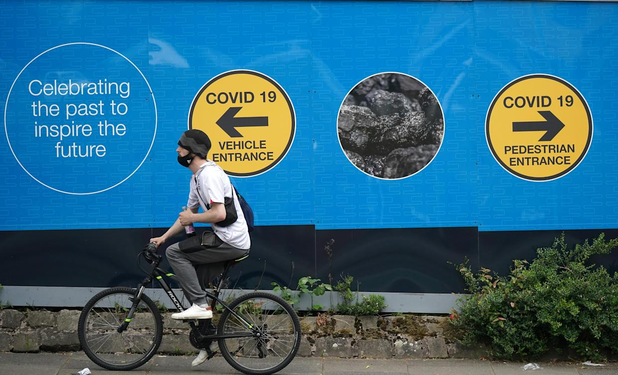 A cyclist passes an advertising board in Bolton, England. (Christopher Furlong/Getty Images)