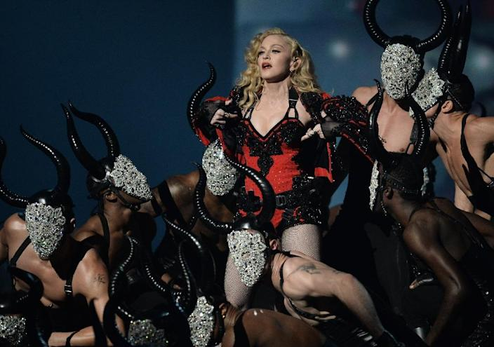 Madonna was performing 'Living For Love' at British pop's top awards ceremony in London Wednesday night when a problem with her floor-sweeping Armani cape caused her to tumble down stairs on the stage (AFP Photo/Robyn Beck)