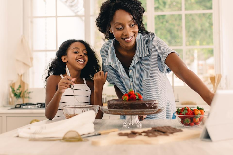 Smiling girl with mother looking at digital tablet while preparing cake in kitchen. Mother and daughter following online recipe while baking cake at home.