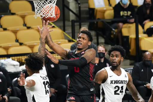 Houston guard Marcus Sasser, center, gets between Central Florida guard Brandon Mahan (13) and guard Dre Fuller Jr. (24) for a shot during the second half of an NCAA college basketball game, Saturday, Dec. 26, 2020, in Orlando, Fla. (AP Photo/John Raoux)