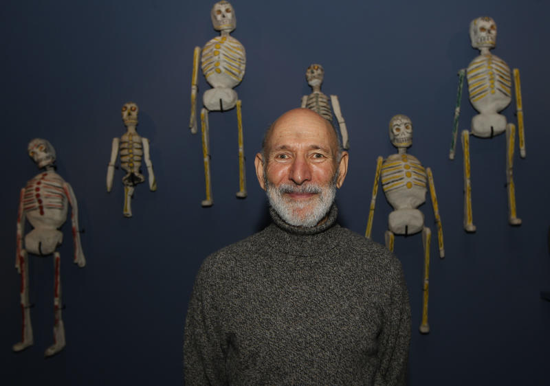 Collector Richard Harris poses with his collection of Mexican 'Day of the Dead' skeletons on display at an exhibition 'Death : The Richard Harris Collection' at the Wellcome Collection gallery in London, Wednesday, Nov. 14, 2012. (AP Photo/Sang Tan)