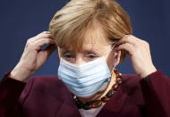German Chancellor Angela Merkel puts on her face mask after holding a joint news conference with Finance Minister Olaf Scholz after a virtual G20 summit meeting, at the Chancellery in Berlin, Germany, Sunday Nov. 22, 2020. (Hannibal Hanschke/Pool via AP)