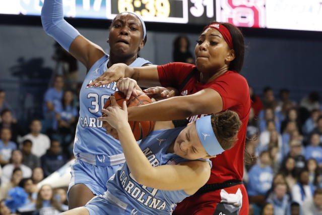 North Carolina guard Leah Church, bottom and center Janelle Bailey (30) struggle for a rebound with North Carolina State center Erika Cassell during the first half of an NCAA college basketball game in Chapel Hill, N.C., Thursday, Jan. 9, 2020. (AP Photo/Gerry Broome)