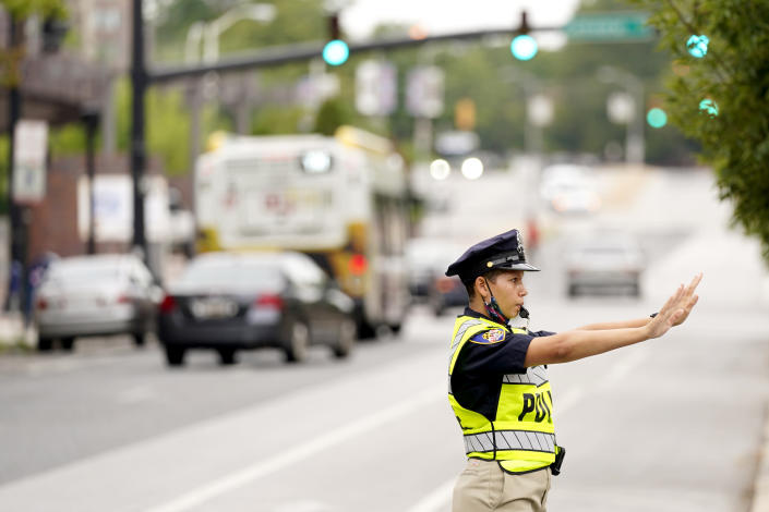 In this Sept. 9, 2020, photo a cadet in the Baltimore Police Academy directs traffic during an on the field class session in Baltimore. (AP Photo/Julio Cortez)