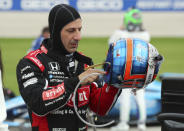 """FILE - Tony Kanaan gets ready to put on his helmet before the IndyCar Series race at Texas Motor Speedway in Fort Worth, Texas., in this Saturday, May 1, 2021, file photo. With nine career starts at Gateway, Kanaan has the most experience at the track of any driver in the field. """"My last IndyCar race of the season, so kind of sad,"""" said Kanaan, who has a two-year deal to run the ovals for Ganassi. """"But excited to go to St. Louis and get Ganassi and the 48 car a win."""" (AP Photo/Richard W. Rodriguez, File)"""