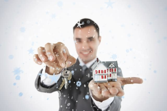 Close up of keys and miniature house being held by male estate agent against snow falling