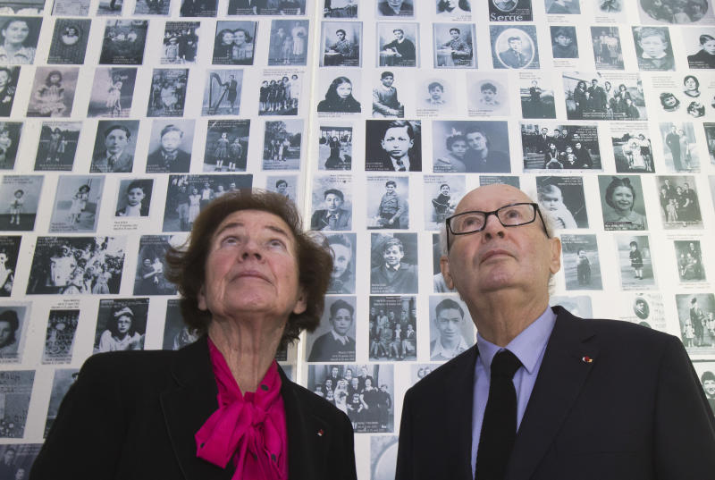 """In this Tuesday, Dec. 5, 2017 photo, French Nazi hunters Beate Klarsfeld and her husband Serge Klarsfeld look at at photos of young Jews deported from France at the Shoah Memorial in Paris, France. The story of Nazi hunters Beate and Serge Klarsfeld is well known in many ways _ and has even spawned a Hollywood movie. Yet, not all has been told of the steely married couple's quest to bring down some of the Third Reich's most infamous villains including Klaus Barbie, the so-called """"Butcher of Lyon."""" Paris' Shoah Memorial is this week hosting the world's first ever exhibit into their story _ called """"Beate and Serge Klarsfeld, Fighters for Memory."""" (AP Photo/Michel Euler)"""