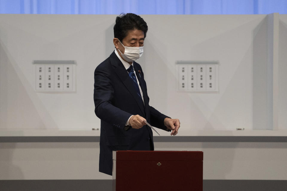Japan's former Prime Minister Shinzo Abe casts his vote in the Liberal Democrat Party leadership election in Tokyo Wednesday, Sept. 29, 2021. Japan's former Foreign Minister Fumio Kishida won the governing party leadership election on Wednesday and is set to become the next prime minister, facing the imminent task of addressing a pandemic-hit economy and ensuring a strong alliance with Washington to counter growing regional security risks. (Carl Court/Pool Photo via AP)