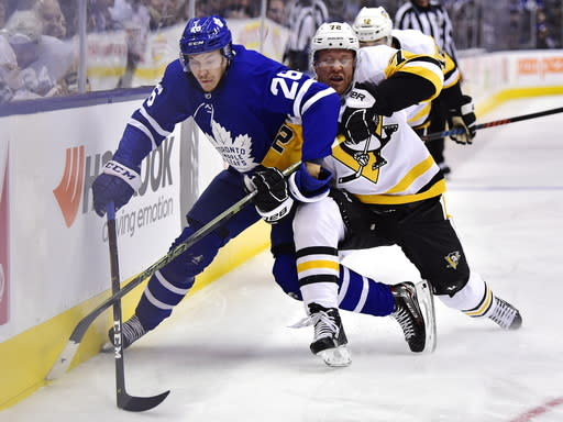 Toronto Maple Leafs center Par Lindholm (26) and Pittsburgh Penguins right wing Patric Hornqvist (72) battle for the puck during first period NHL hockey action in Toronto on Thursday, Oct. 18, 2018. (Frank Gunn/The Canadian Press via AP)