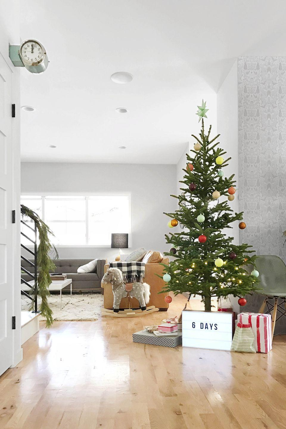 """<p>If the <em>Peanuts </em>movie taught us anything, it's that you don't need a big over-the-top spruce to find the """"true meaning of Christmas."""" If your prefer a minimalist Christmas decorating vibe, opt for a simple faux tree decorated with a handful of colorful ornaments.</p>"""