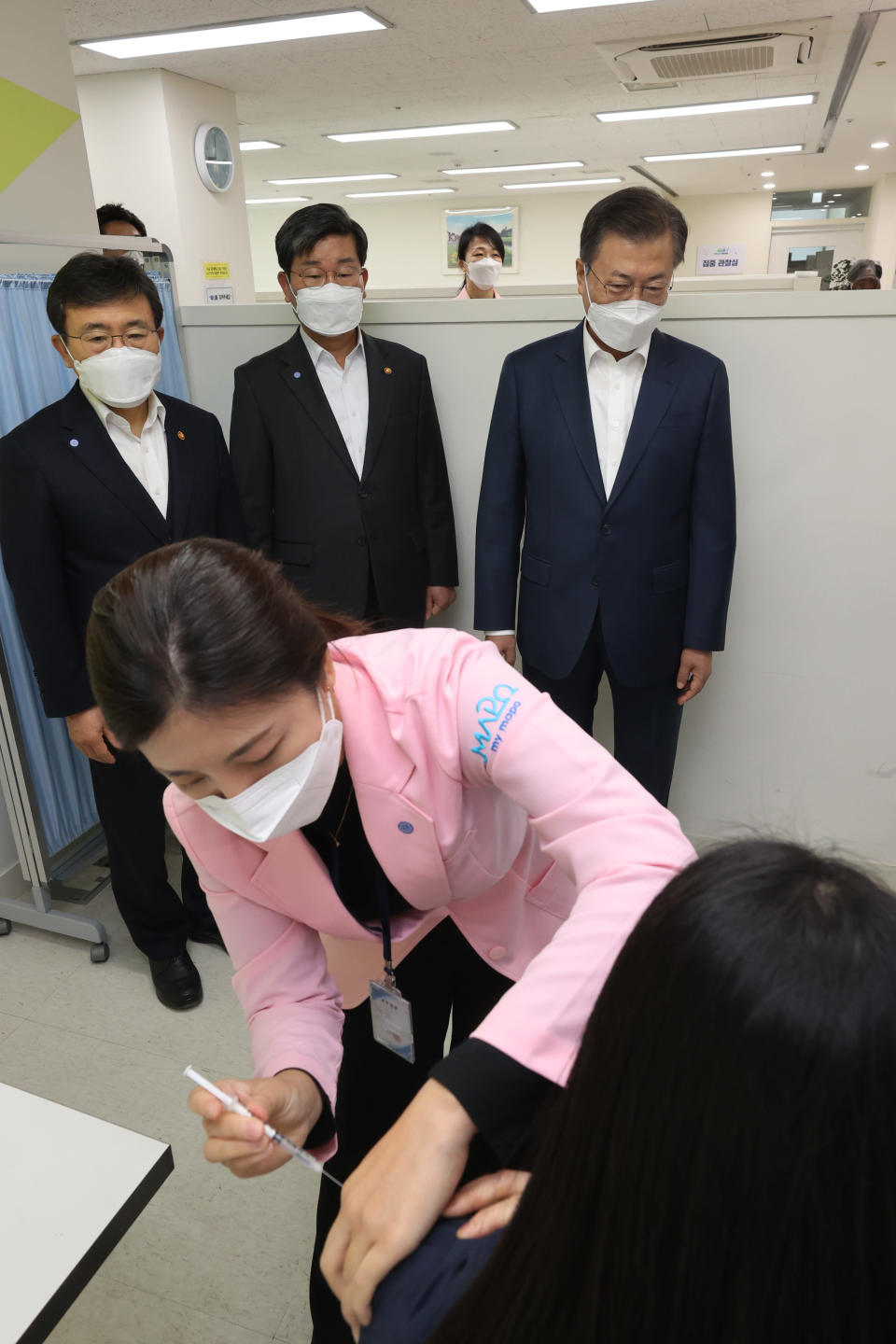 South Korean President Moon Jae-in, rear right, watches a doctor receives a shot of AstraZeneca vaccine at a public health center in Seoul, South Korea, Friday, Feb. 26, 2021. South Korea on Friday administered its first available shots of coronavirus vaccines to people at long-term care facilities, launching a mass immunization campaign that health authorities hope will restore some level of normalcy by the end of the year.(Choe Jae-koo/Yonhap via AP)