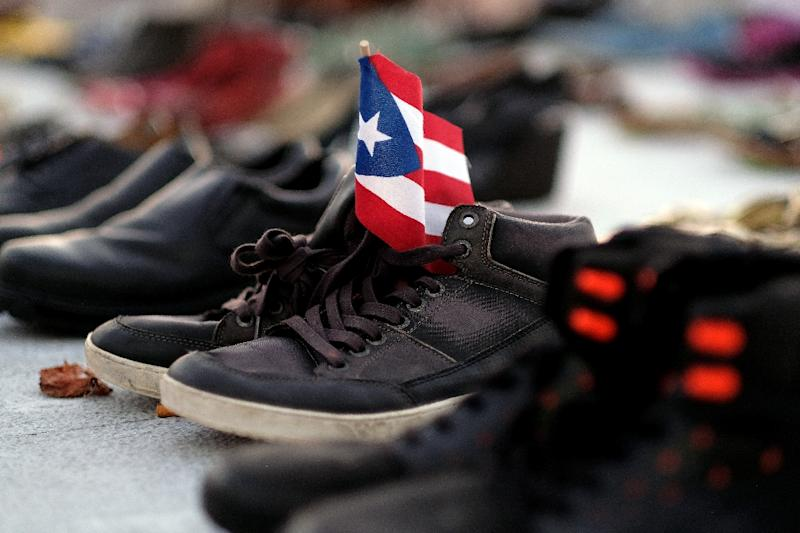 View of a Puerto Rican flag placed on a pair of shoes among hundreds displayed in memory of those killed by Hurricane Maria in front of the Puerto Rican Capitol, in San Juan on June 1, 2018 (AFP Photo/Ricardo ARDUENGO)