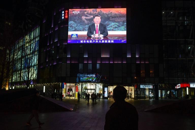 People walk below a giant screen at a shopping mall in Beijing showing news coverage of Chinese President Xi Jinping's speech to the virtual APEC summit